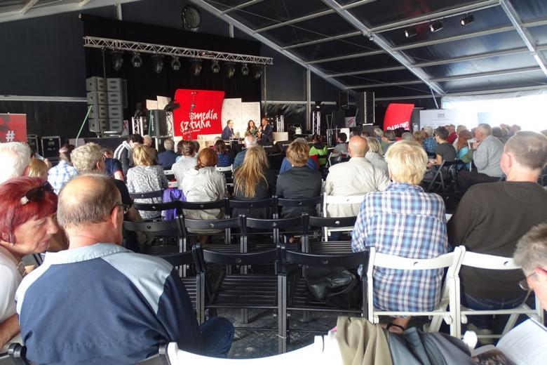 Zdjęcie: ludzi siedzą i słuchają debaty w namiocie - na scenie trzy osoby
