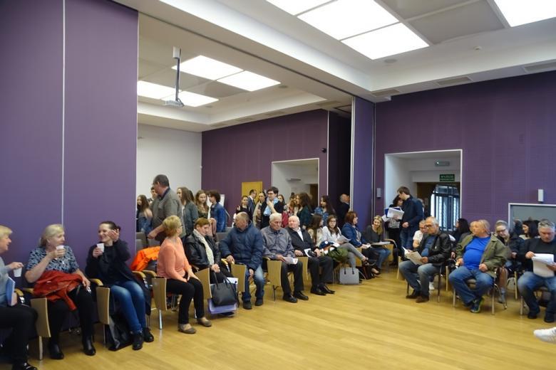 Dużo osób na sali, fioletowa przesuwna ściana jest demontowana