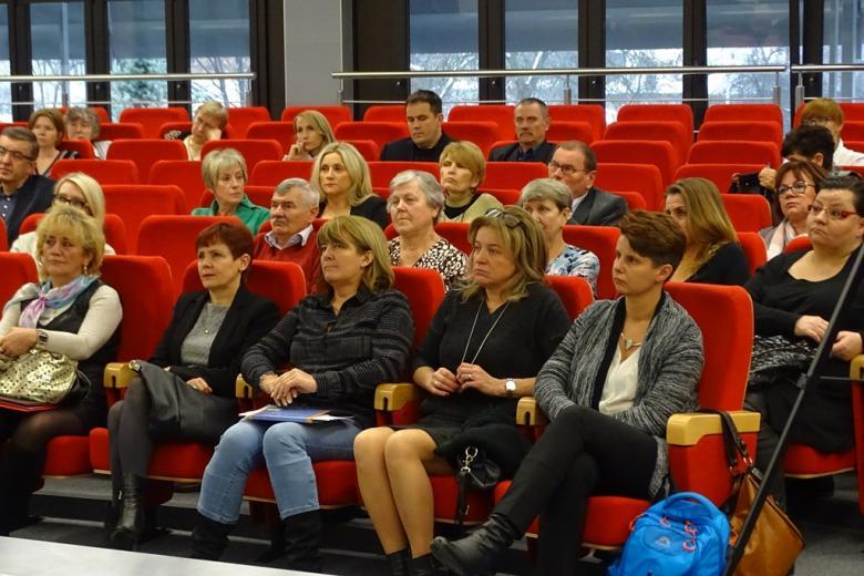 Zdjęcie: ludzie siedzą na czerwonych fotelach w sali audytoryjnej