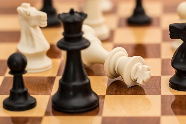 Szachy. Pion białego króla leży przed czarną królową