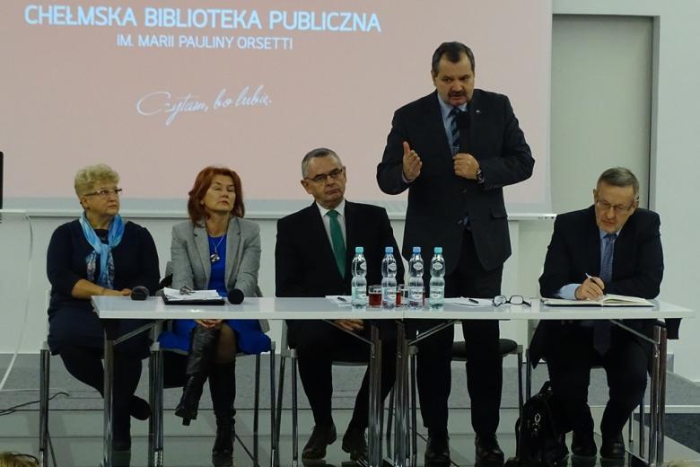 """Zdjęcie: prezydium, mężczyzna stoi. W tle - napis """"Bibliotek Publiczna"""""""