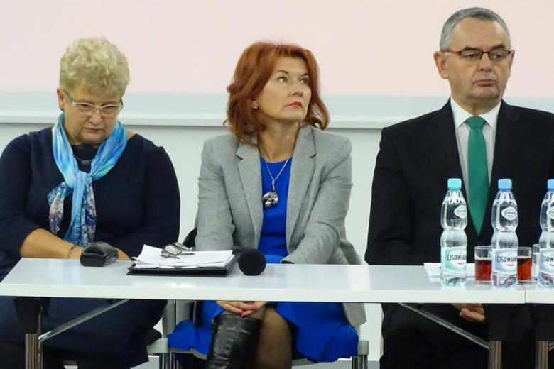 Zdjęcie: dwie kobiety i mężczyzna siedzą za stołem prezydialnym