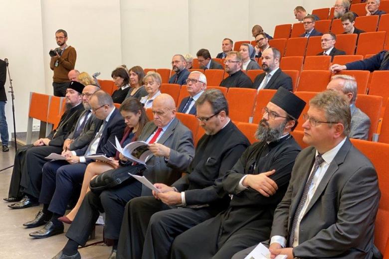 Ludzie na sali audytoryjnej, w tym ksiądz prawosławny