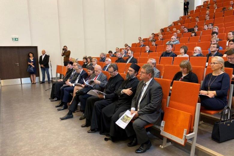 Ludzie na sali audytoryjnej, w tym ksiądz prawosławny, szersze ujęćie