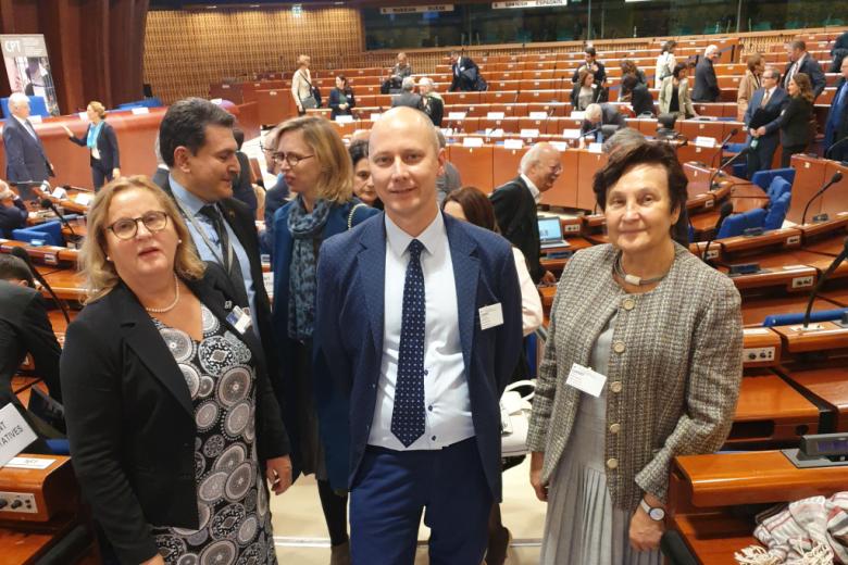 Dwie kobiety i mężczyzna pozują do zdjęcia na tel sali obrad Rady Europy