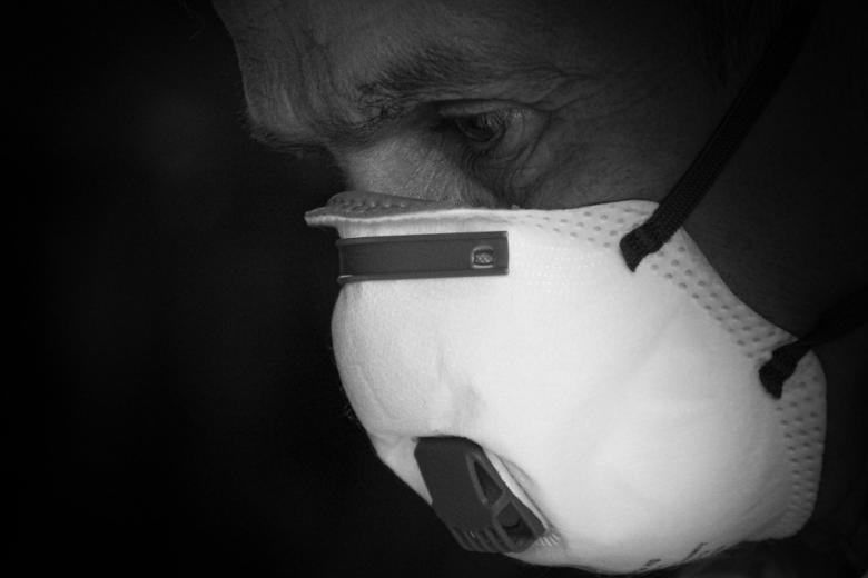 Czarno-białe zdjęcie człowieka z twarzą zasłoniętą maską
