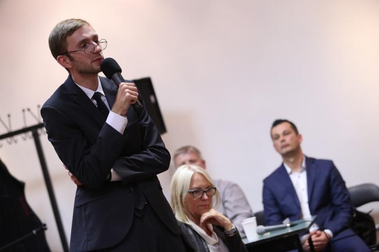 Mężczyzna w okularach mówi do mikrofonu
