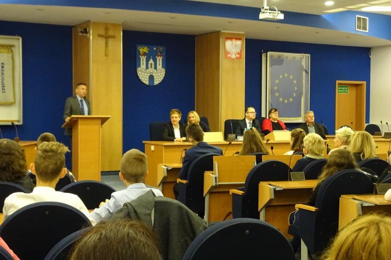 Sala obrad rady miasta, na miejscach radnych uczniowie, kilka osób w prezydium