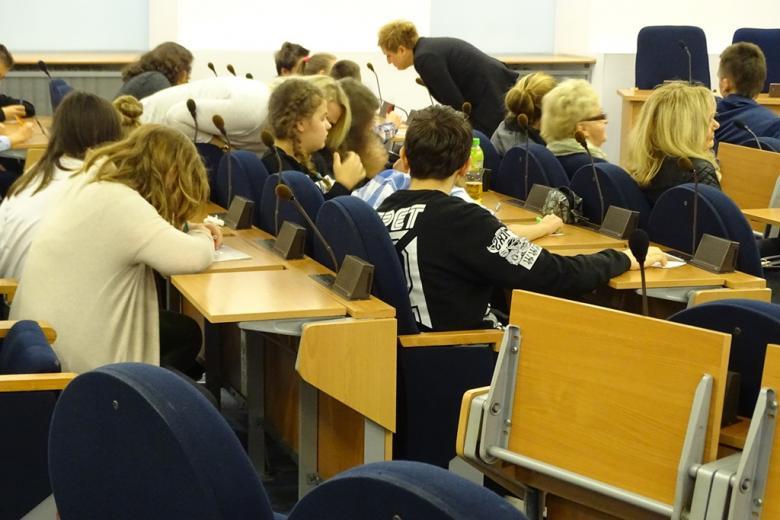 Młodzi ludzie piszą na kartkach w sali obrad rady miasta