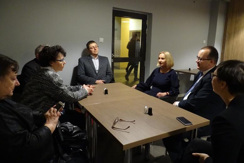 Kilka osób rozmawia przy zsuniętych stolikach