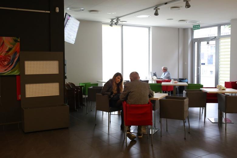 Kobieta i mężczyzna rozmawiają; meżczyzna sfotografowany od tyłu
