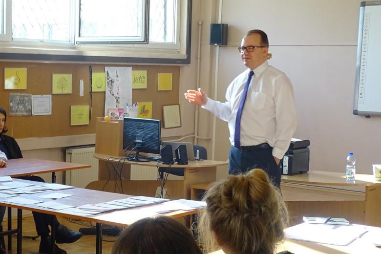 Mężczyzna w klasie przed stołem, na którym leżą kartki