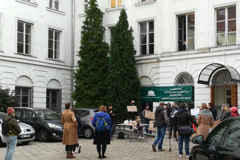 Kilka osób z transparentami przed budynkiem