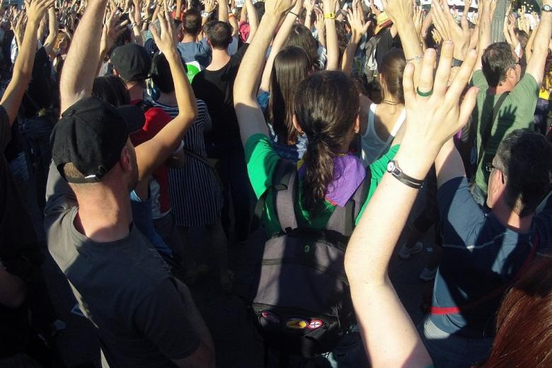 Ludzie w czasie zgromadzenia wznoszą ręce