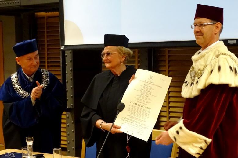 zdjęcie: trzy osoby w togach stoją za stołem, kobieta w środku trzyma dyplom