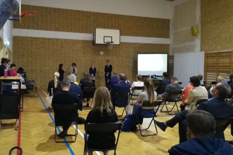 Cztery osoby stoją przed ludźmi zebranymi w sali gimnastycznej