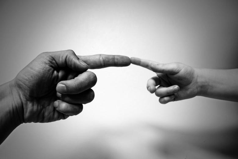 """Ręka dziecka i dorosłego w geście """"stworzenia świata"""""""
