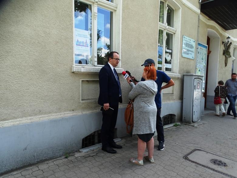 Meżczyzna stoi na ulicy i odpowiada na pytania dwojga dziennikarzy, którzy mają mikrofony