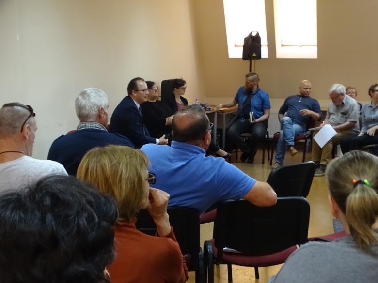 Grupa ludzi siedzi na sali i rozmawia