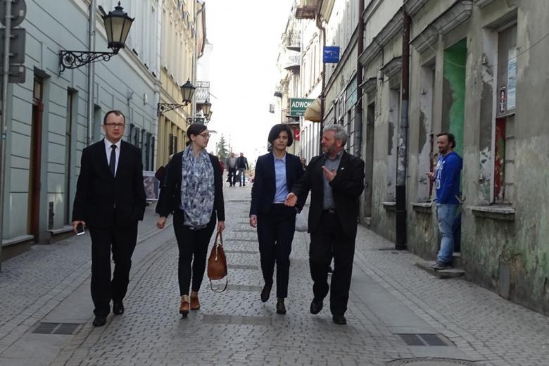 Grupa ludzi idzie ulicą i rozmawia