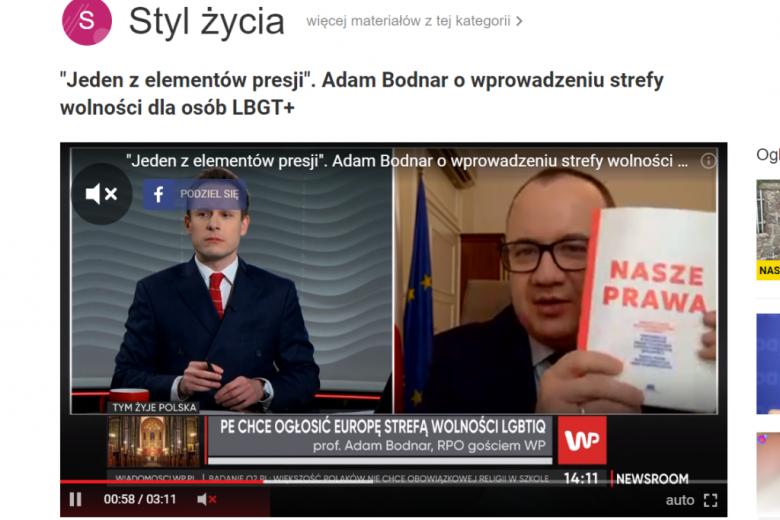 """Screen: dwaj mężczyźni na ekranie, jeden pokazuje książkę """"Nasze prawa"""""""