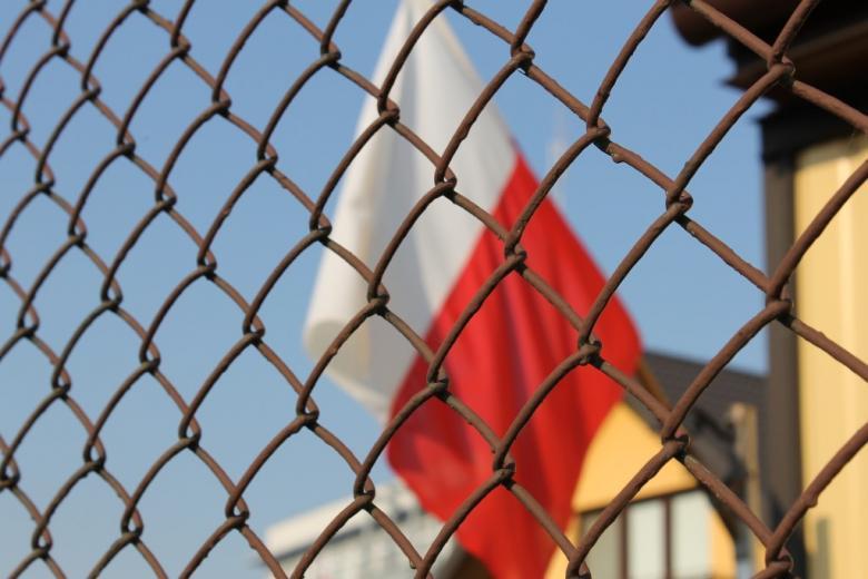 Polska flaga za siatką ogrodzenia