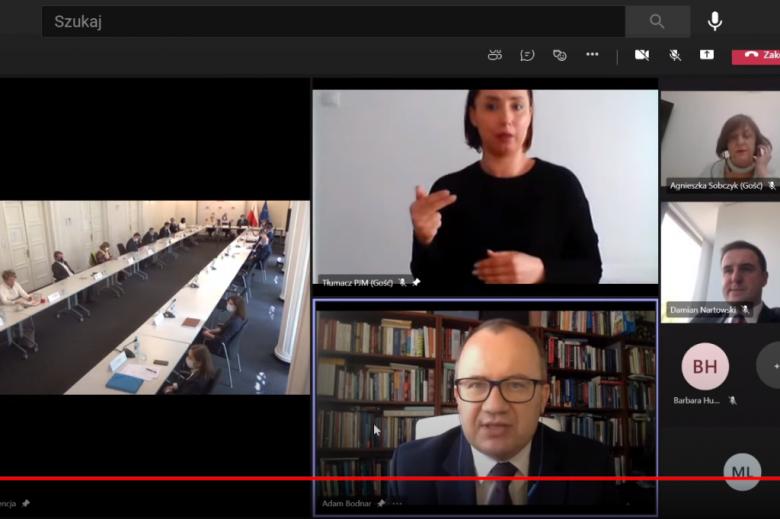 Screen: ludzie na sali, uczestnicy debaty online oraz tłumaczka języka.pl