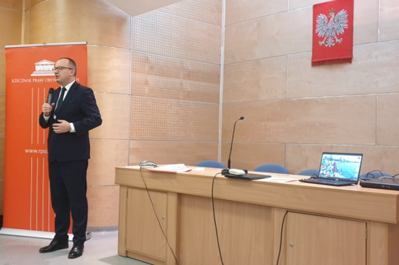 Mężczyzna przemawia na stojąco w sali wykladowej