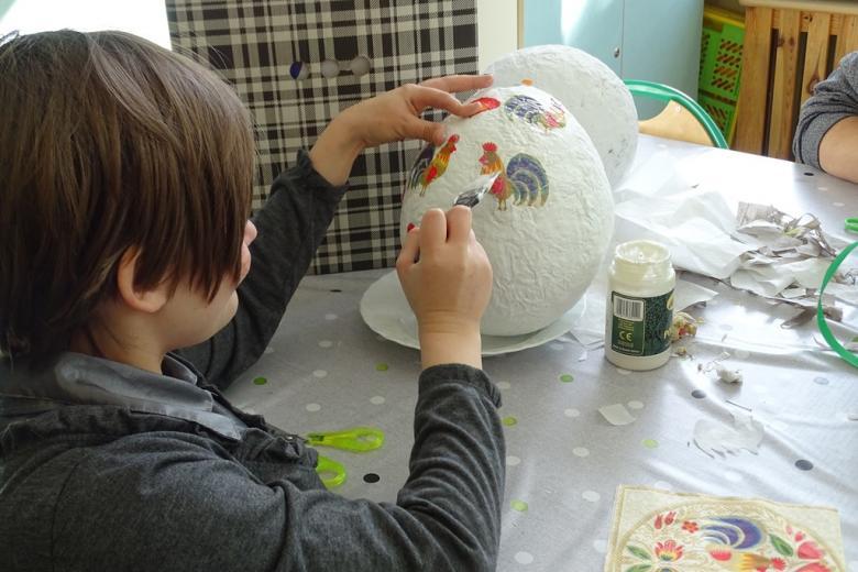Dziecko dekoruje duża pisankę ze styropianu