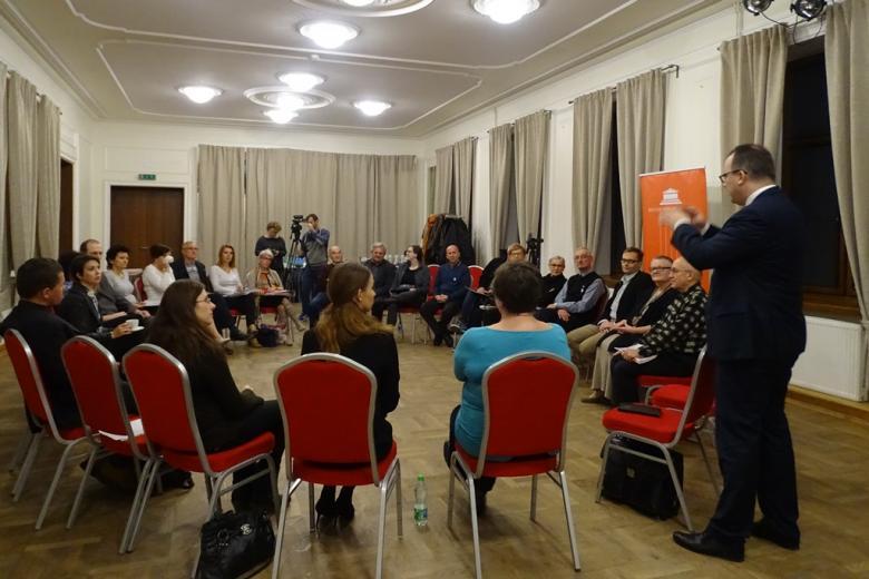 Zdjęcie: ludzie siedzą w kręgu, mężczyzna stoi i gestykuluje