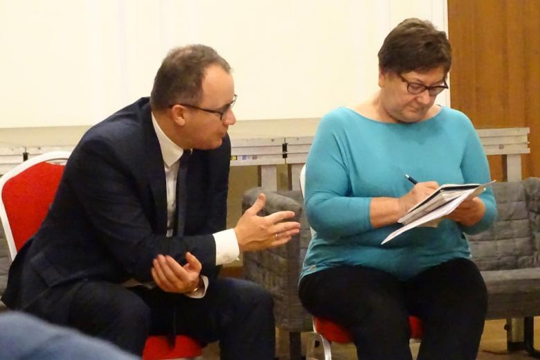 Zdjęcie: mężczyzna słucha, kobieta notuje