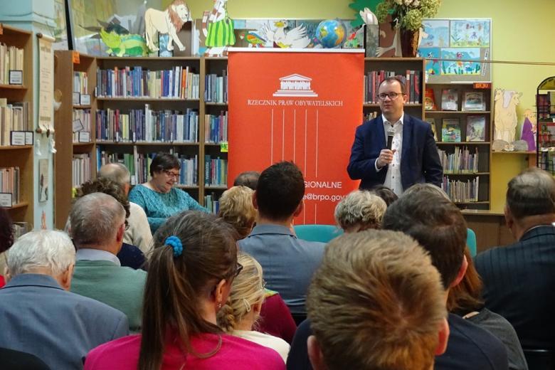 Zdjęcie: ludzie w sali bibliotecznej, zbliżenie na mówiącego męzczyznę