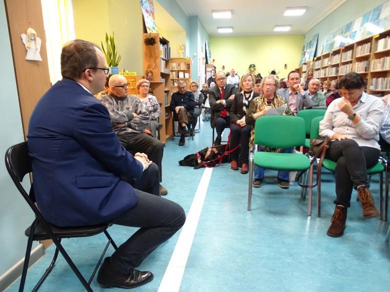 Zdjęcie: spotkanie regionalne: męzczyzna siedzu i słucha, kobieta mówi, na podłodze leży pies przewodnik osoby niewidomej
