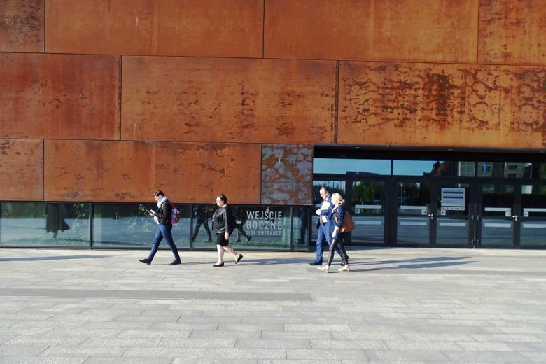 Ludzie wychodzą z budynku o rudych metalowych ścianach