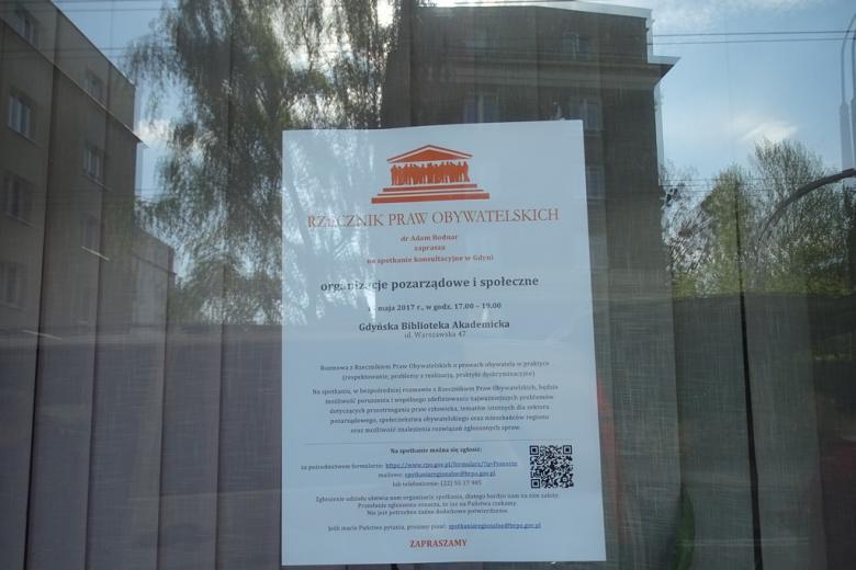 Plakat informacyjny na szybie, odbijają się w niej budynki z lat 60. i 50. XX wieku