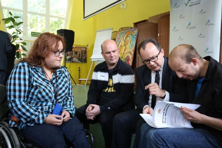 Trzy osoby rozmawiają oglądając broszurę