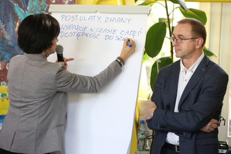 Kobieta pisze na tablicy, obok mężczyzna