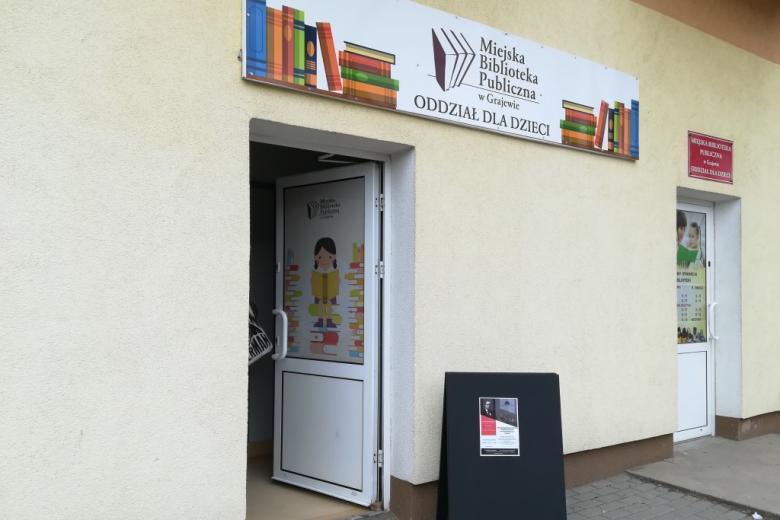 Wejście do biblioteki z plakatem o spotkaniu z Adamem Bodnarem