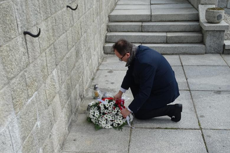 Mężczyzna klęcząc kładzie biało-czerwone kwiaty pod pomnikiem