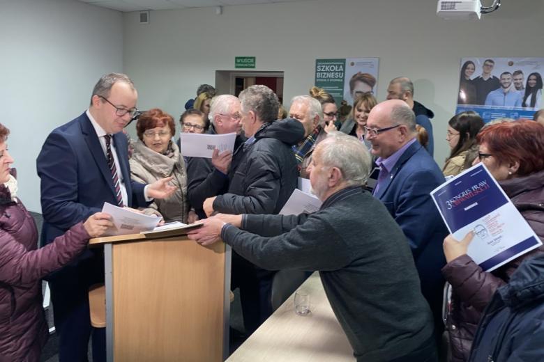 Mężczyzna składa podpisy pod dokumentem