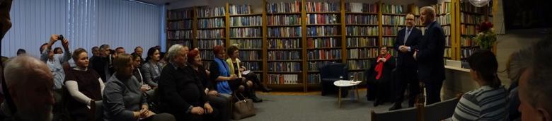 Kilkadziesiąt osób w bibliotece, dwaj mężczyźni stoją