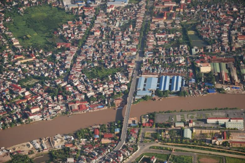 Miasto nad rzeką z wodą w kolorze czerwonawym. Widok z góry