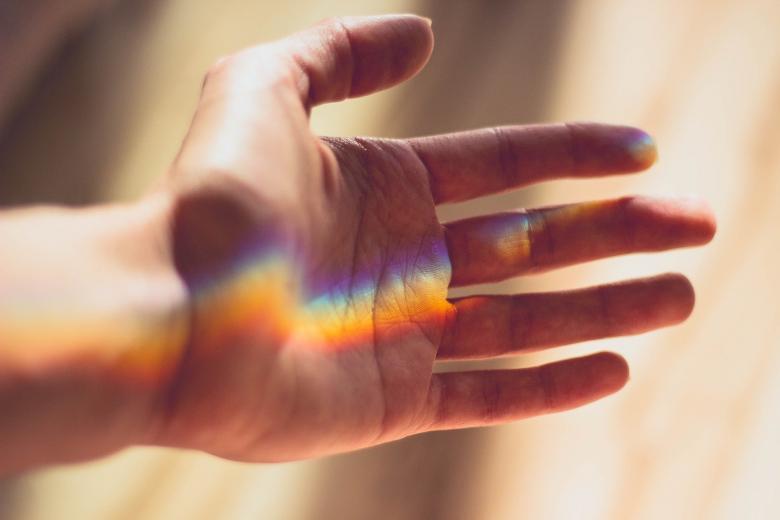 Ręka z rozszczepionym światłem w kolorach tęczy