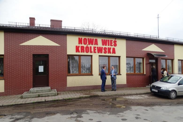 Dwaj mężczyźni przed budynkiem z napisem Nowa Wieś Królewska