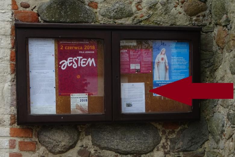 Gablota z ogłoszeniami parafialnymi, na jednym z plakatów wizerunek Matki Boskiej
