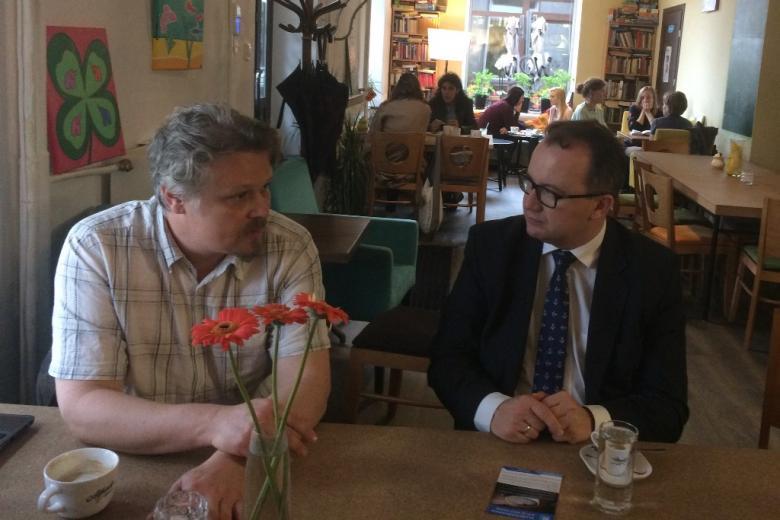 zdjęcie: dwóch mężczyzn siedzi przy stoliku