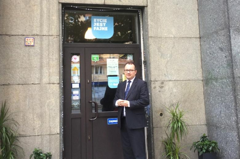 zdjęcie: mężczyzna w garniturze stoi przy wejściu do kawiarni
