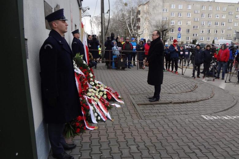 zdjęcie: mężczyzna stoi przed tablicą pod którą leżą biało-czerwone kwiaty