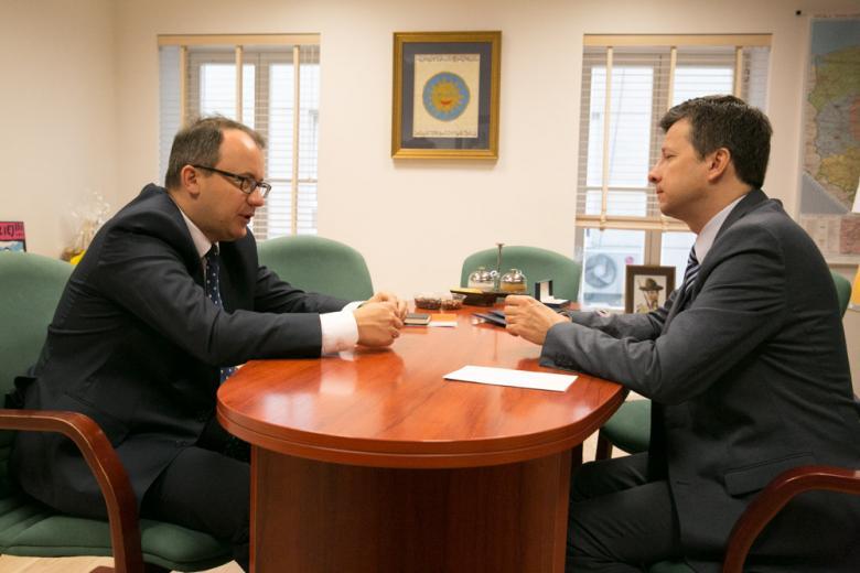 zdjęcie: dwóch mężczyzn w garniturach siedzi naprzeciwko siebie przy stole