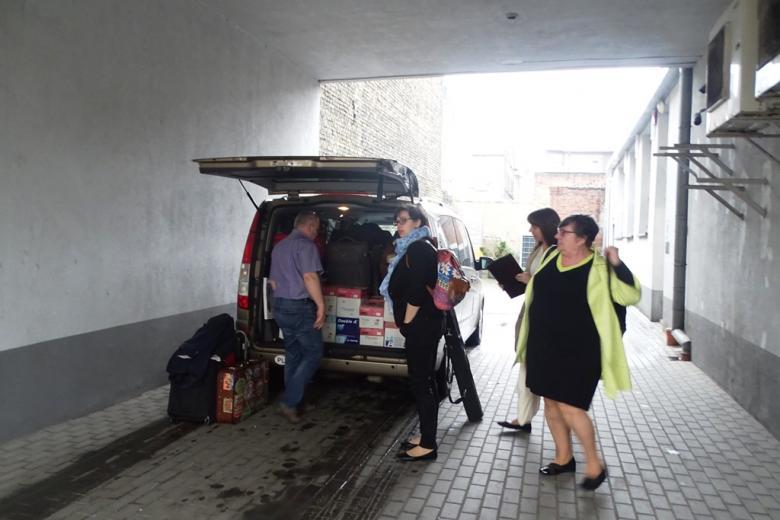 Minibus w bramie, ludzie wyjmują paczki z publikacjami z bagażnieka